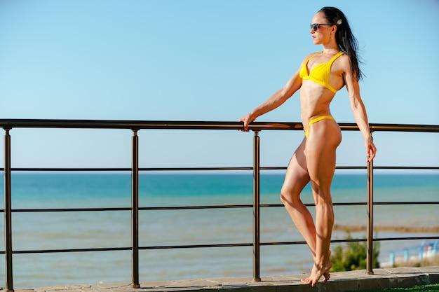 Modelo de fitness mulher morena em trajes de banho posando à beira-mar