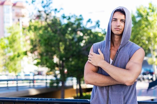 Modelo de fitness musculoso atlético bonito fisiculturista posando após exercícios ao ar livre