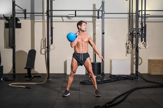 Modelo de fitness musculoso e atlético fisiculturista posando após exercícios na academia