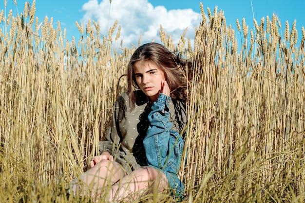 Modelo de garota linda em um vestido na zona rural. no contexto de um campo de trigo. céu azul, liberdade e conceito de verão quente.