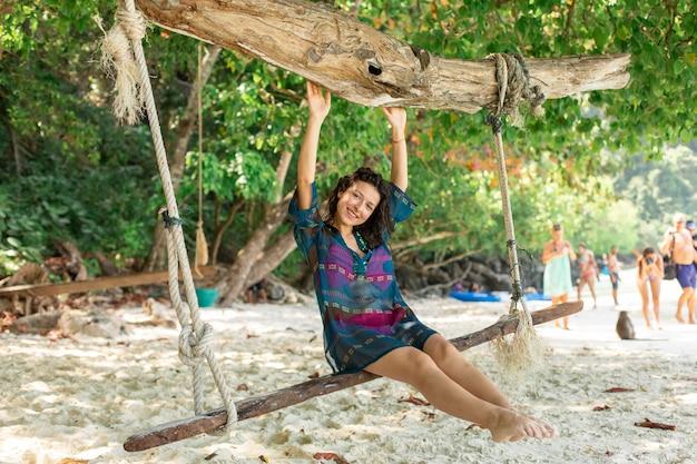 Modelo de garota sexy descansando enquanto andava em um balanço amarrado a uma árvore em uma ilha tropical.