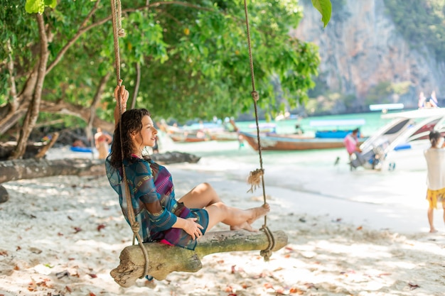 Modelo de garota sexy slim em fato de banho posando em um balanço de madeira amarrado a uma árvore.