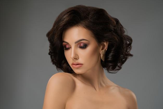 Modelo de glamour com sombra brilhante, cabelos ondulados.