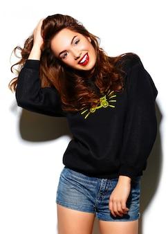 Modelo de glamour feliz sorridente mulher jovem e bonita elegante com lábios vermelhos em pano preto azul hipster