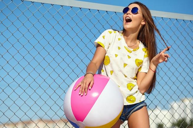 Modelo de glamour louco elegante elegante sorridente mulher jovem e bonita em roupas casuais de verão hipster brilhante posando na rua atrás de grade de ferro e céu azul. brincando com bola inflável colorida floa