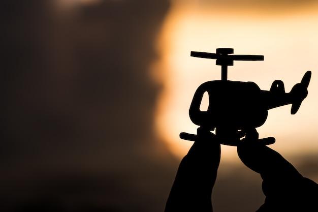 Modelo de helicóptero nas mãos da silhueta no céu da luz solar.
