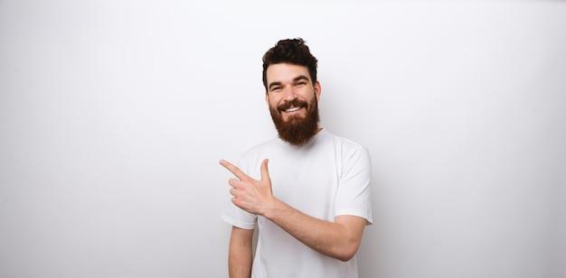 Modelo de homem barbudo bonito em branco no branco, apontando de lado em um espaço em branco da cópia para o seu texto.