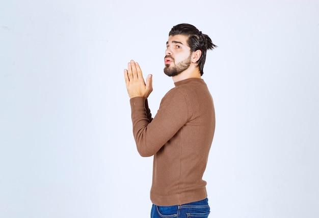 Modelo de homem bonito olhando para cima e de mãos dadas.