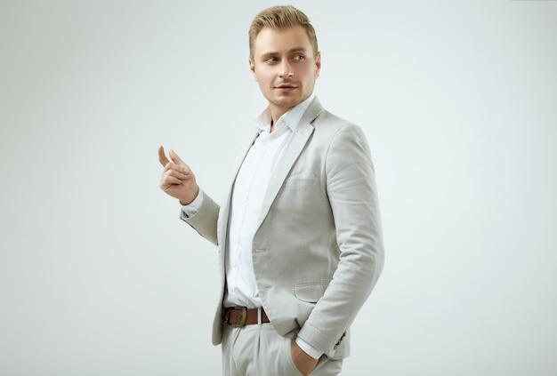 Modelo de homem loiro bonito em um terno cinza de moda em estúdio