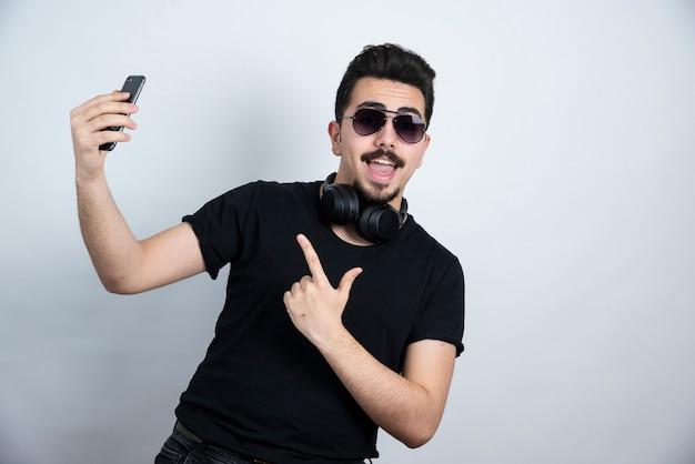 Modelo de homem morena de pé em fones de ouvido e segurando o telefone móvel.