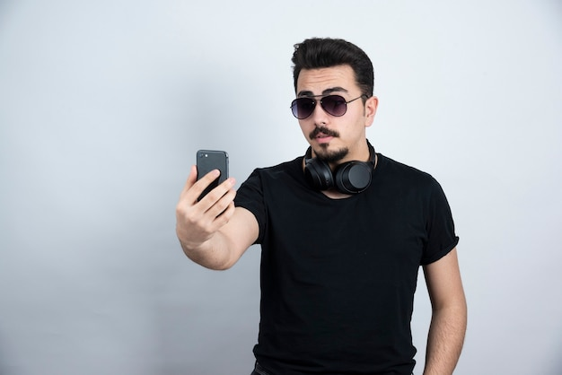 Modelo de homem moreno em fones de ouvido e tomando selfie.