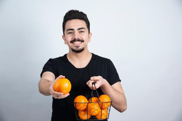 Modelo de homem moreno em pé e posando com frutas laranja.