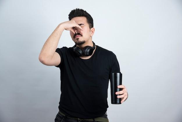 Modelo de homem moreno segurando uma xícara e fechando o nariz com nojo.