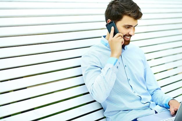 Modelo de jovem empresário sorridente bonito sentado no banco do parque em pano casual hipster falando no celular