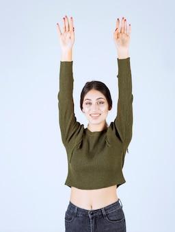 Modelo de jovem feliz em pé e levantando as mãos.