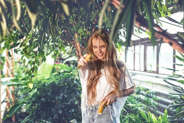 Modelo de jovem loira linda e feliz com bananas em fundo de plantas tropicais.