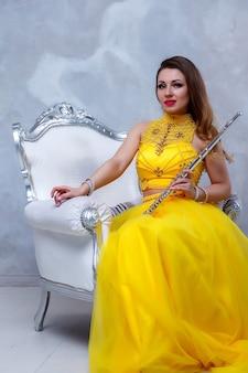 Modelo de jovem retrato no palco amarelo vestido com flauta nas mãos. instrumento de sopro no flautista no fundo da parede texturizada. cartaz para escola de publicidade. música conceitual ou concerto