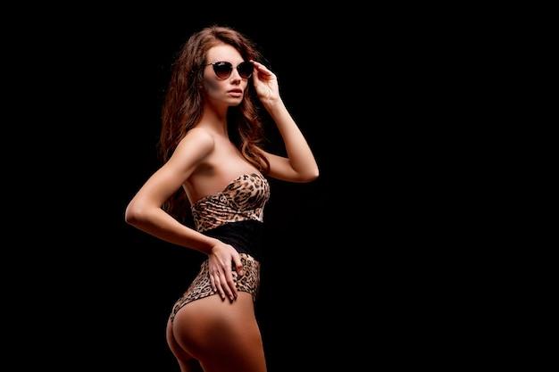 Modelo de lingerie sexy posando em um estúdio com um maiô chita isolado no fundo preto