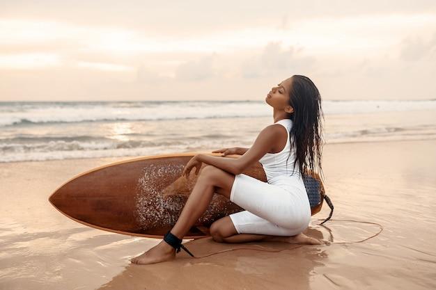 Modelo de luxo jovem em um terno de surf branco posando sentado à beira-mar com uma prancha de surf. pôr do sol lindo mar