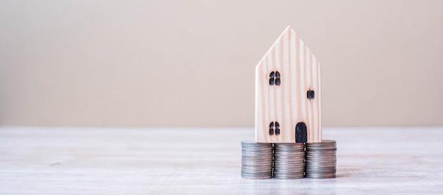 Modelo de madeira da casa sobre a pilha das moedas no fundo da tabela.