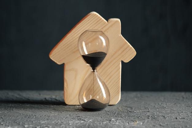 Modelo de madeira de close-up de casa e ampulheta. salvando e comprando um conceito de propriedade.