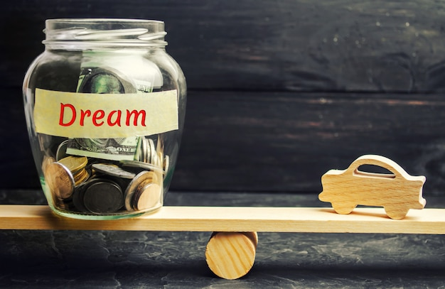 Modelo de madeira do carro e um frasco de vidro com moedas e a inscrição dream