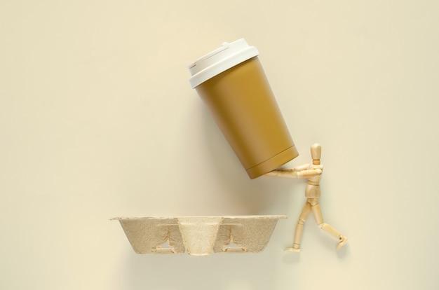 Modelo de madeira segurando copo de café reutilizável para colocar na bandeja de papel reciclado