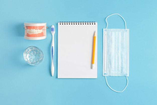 Modelo de mandíbula com escova de dentes e mesa de dentista com bloco de notas