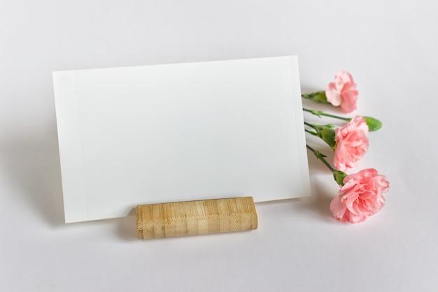 Modelo de maquete com cartão de foto em branco vazio e três flores cor de rosa na superfície branca.