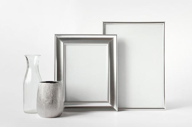 Modelo de maquete com duas molduras de prata em branco, pequenos vasos de prata e vidro em fundo branco.