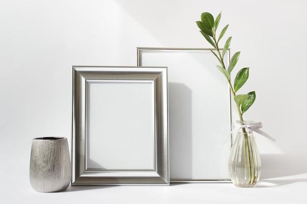 Modelo de maquete com duas molduras de prata em branco, vaso pequeno de prata e ramo de planta zamioculcas verde em vaso de vidro.