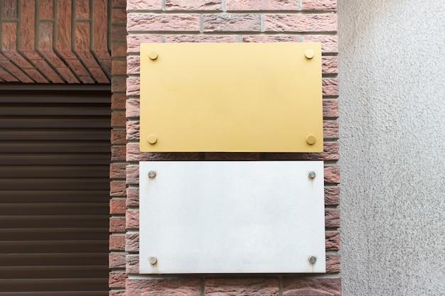 Modelo de maquete com duas placas brancas metálicas cinza e amarelas na fachada do prédio