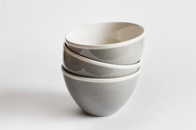 Modelo de maquete com três pratos de tigelas de porcelana empilhados na superfície branca.