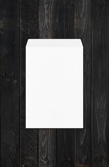 Modelo de maquete de envelope branco grande a4 isolado em fundo preto de madeira