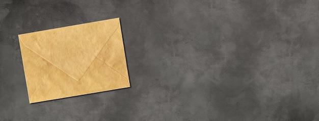 Modelo de maquete de envelope de papel pardo isolado em banner horizontal de concreto