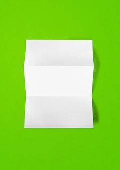 Modelo de maquete de folha de papel branco a4 dobrado em branco isolado em fundo verde