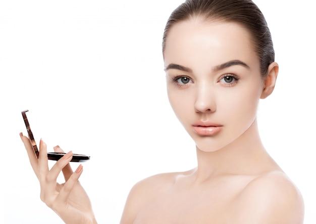 Modelo de maquiagem beleza segurando a base do pó