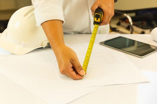 Modelo de medição da mão da arquitetura com masure da fita na tabela de funcionamento.
