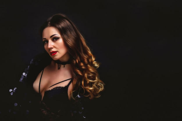 Modelo de meia-idade envelhecido jovem retrato em traje preto de palco vestido posando em fundo preto. rosto de mulher bonita com maquiagem fashion e cabelos longos. papel de parede para anúncio. conceito de beleza e saúde
