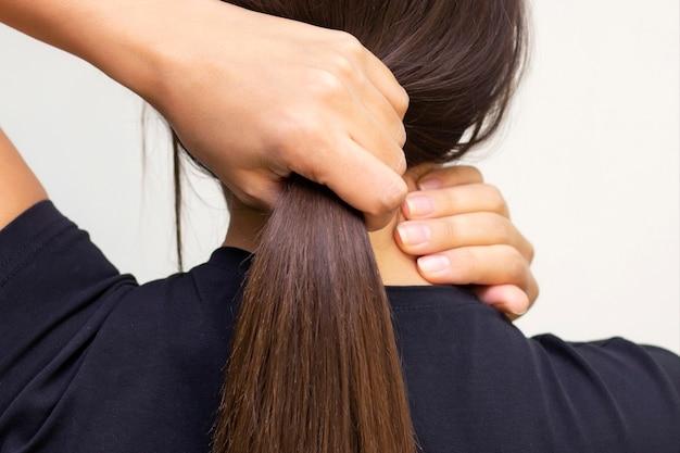 Modelo de menina bonita com cabelo comprido liso castanho brilhante. produtos para o cuidado do cabelo. mantém o cabelo em um punho, força do cabelo