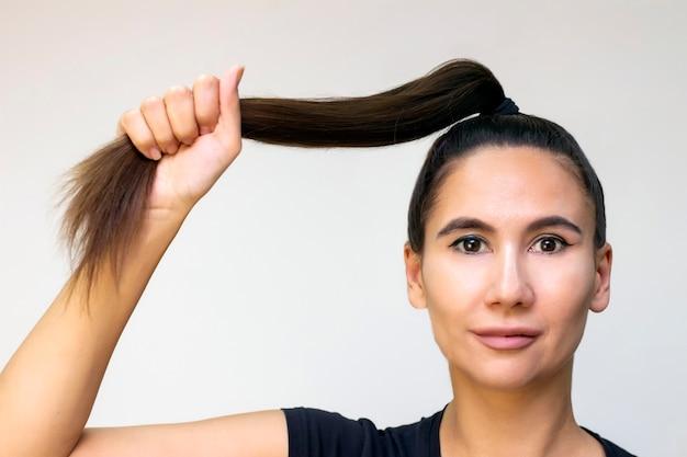 Modelo de menina bonita com cabelo comprido liso castanho brilhante. produtos para os cabelos. mantém o cabelo em punho, força do cabelo