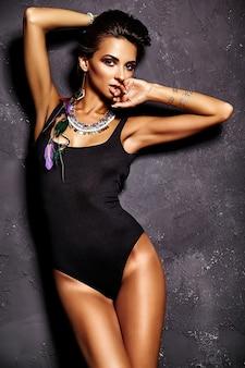 Modelo de menina bonita em lingerie preta verão com maquiagem criativa brilhante posando perto de parede cinza