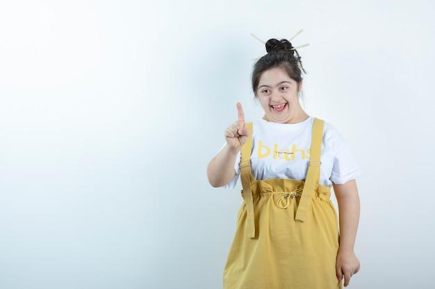 Modelo de menina bonita jovem em pé e apontando o dedo para a câmera contra uma parede branca.