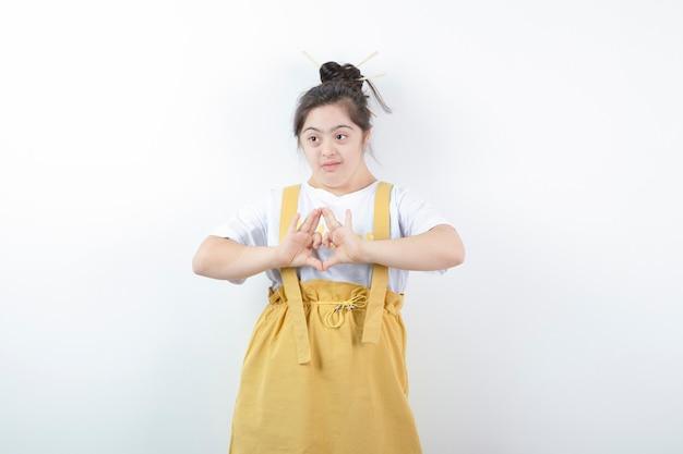 Modelo de menina bonita jovem em pé e fazendo o símbolo do coração com as mãos contra uma parede branca.