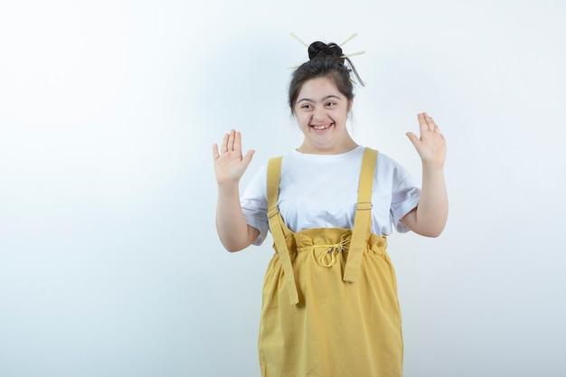 Modelo de menina bonita jovem em pé e posando contra uma parede branca.