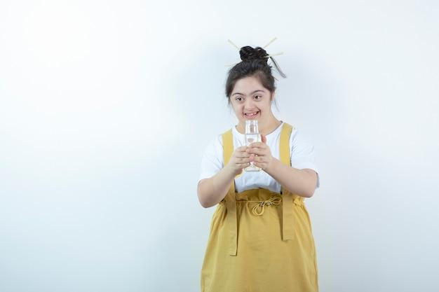 Modelo de menina bonita jovem em pé e segurando o frasco de vidro contra a parede branca.