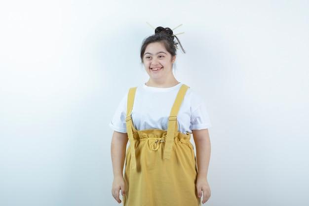 Modelo de menina bonita jovem em pé e sorrindo amplamente contra uma parede branca.