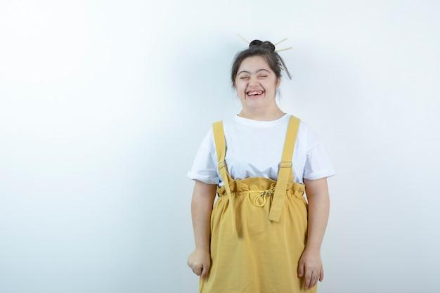 Modelo de menina bonita jovem em pé e sorrindo contra uma parede branca.