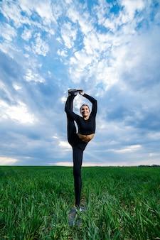 Modelo de menina bonita na grama verde fazer ioga. uma bela morena em um gramado verde executa elementos acrobáticos. ginasta flexível de preto fazendo exercícios