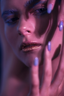 Modelo de menina elegante em tons de néon com maquiagem brilhante mantém as mãos no rosto.